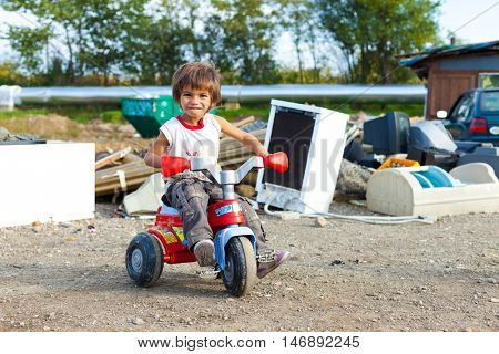 ZAGREB, CROATIA - OCTOBER 21, 2013: Cute little Roma boy sitting on small bike in front of street garbage dump.
