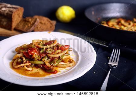 Calamar with tomato and chilli sauce in white dish on dark wood background. Plate with dish and bread on bacground