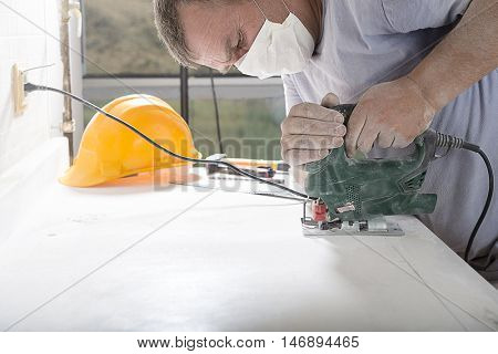 Man cutting kitchen counter top using electric jig saw with space for your text.