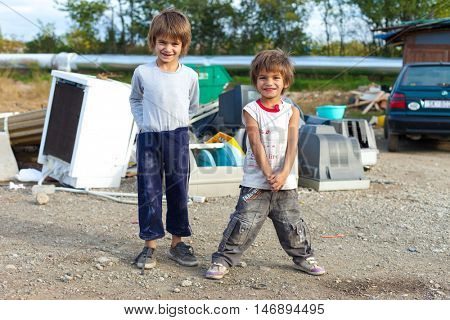 ZAGREB, CROATIA - OCTOBER 21, 2013: Cute little Roma boys standing in front of street garbage dump.
