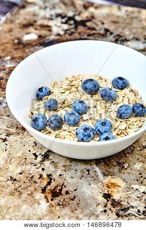 Raw oat flakes topped fresh blueberries in white bowl. Organic food on metal, grunge background. Dietary, tasty ingredients for delicious and healthy breakfast Vitamin and energy booster for whole day