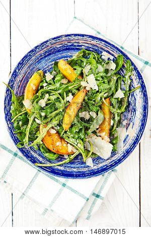 Arugula and peaches salad. Vegetarian gourmet salad made of caramelized grilled peaches slices, arugula leaves, parmesan cheese flakes and soy-vinaigrette dressing, top view. White wood background.