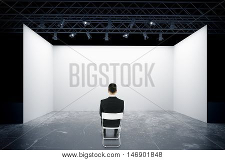 Businessman on chair looking at empty truss stage. Back view 3D Rendering