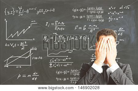 Stressed businessman covering face with palms on chalkboard background with mathematical formulas. Education concept