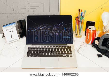 PARIS FRANCE - SEP 8 2016: Apple Computers website on MacBook Retina in room environment showcasing live coverage of Apple Keynote - auditorium full with people
