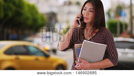 Japanese university student talking on smartphone outdoors. Trying to call a cab. Telling a friend she's running late.