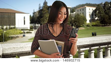 Japanese woman talking on smartphone outdoors on campus. Happy student enjoying her time at college.