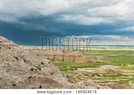 Dark blue storm clouds and bird in Badlands National Park with prairie valley view