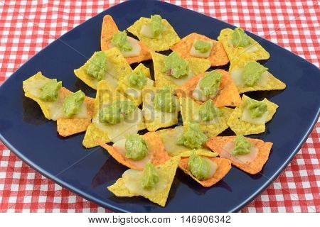 Nachos appetizer with tortilla chips, cheese and guacamole on blue plate