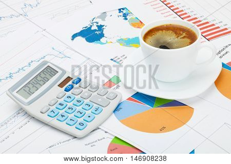 Coffee Cup And Calculator Over World Map And Some Financial Documents - Business Concept