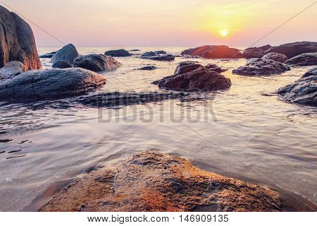 Tropical colourful sunset on the beach Koh Chang island Thailand. View of dark night sea with protruding stones