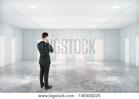 Back view of thoughtful businessman standing in concrete room with many white doors. Success concept
