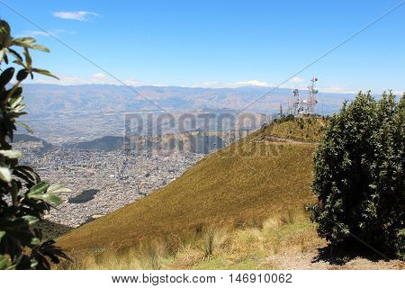 This photo shows a view of the cableway station, the city of Quito on the right and the Cotopaxi Volcano in the background at Quito, Ecuador.