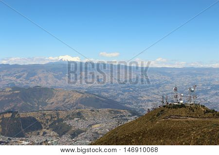 This photo shows a view of the Antisana Volcano in the background, part of the Quito city and the cableway station on Quito, Ecuador.