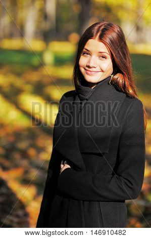 Cute smiling, brown-eyed girl with long brown hair in the autumn forest looking at you.