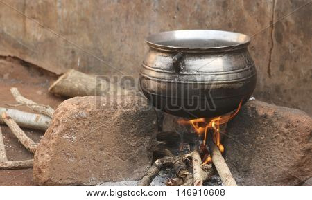 Traditional African outdoor cooking area with cauldron over open wood fire