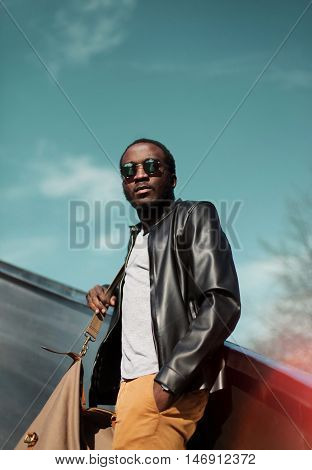 Fashion Young African Man In City Wearing A Black Rock Leather Jacket With Bag Over Evening Sky