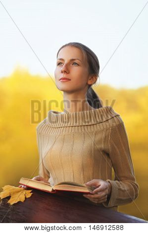 Portrait Young Woman With Book And Yellow Maple Leaf Dreams Outdoors In Warm Sunny Autumn Day