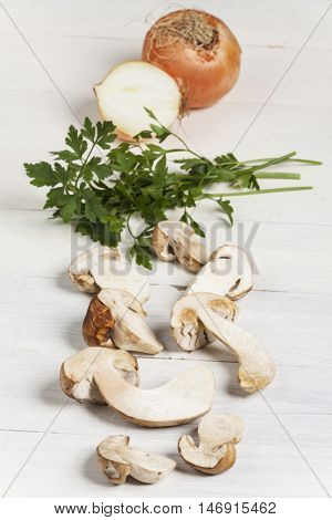 raw porcino mushrooms on white wood with parsley