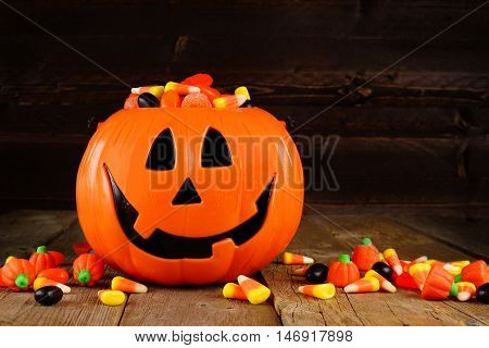Halloween Jack O Lantern Candy Holder With Scattered Candy On Rustic Wood Background