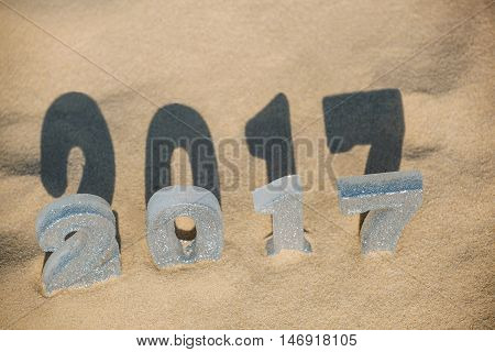 Four New Year's figures are in the sand on the beach or seaside cast a large shadow on the ground. New Year Celebration and Christmas in the ocean the sea. Traveling.