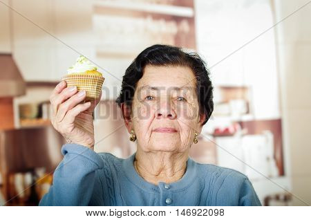 Older hispanic woman wearing blue sweater sitting in front of camera holding up a yellow cupcake with cream topping.