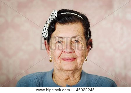 Older cute hispanic woman wearing blue sweater and polka dot bowtie on head smiling carefully in front of pink wallpaper.