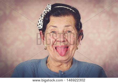 Older cute hispanic woman wearing blue sweater and polka dot bowtie on head showing her tongue to the camera in front of pink wallpaper.