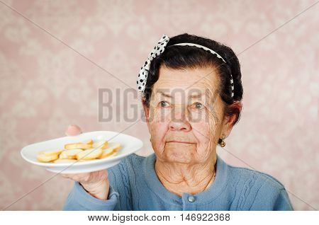 Older cute hispanic woman wearing blue sweater and polka dot bowtie on head holding up a plate of cookies.