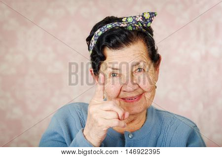 Older cute hispanic woman wearing blue sweater and flower pattern bow on head holding up one finger for the camera in front of pink wallpaper.