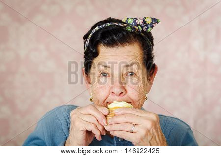 Older hispanic happy woman wearing blue sweater and flower pattern bow on head sitting in front of camera having a bite off cupcake.