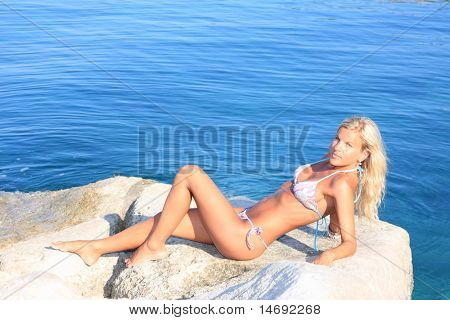 Beautiful young blond woman by the sea