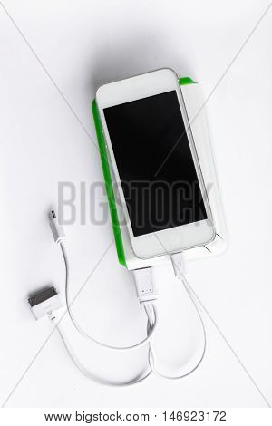 power bank charging power to smart phone on white background