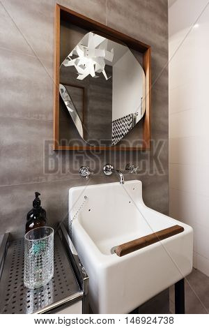 White vintage vanity basin with wood detail and mirror against grey tiled wall
