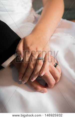 Newly married bride and groom place hands together with rings showing