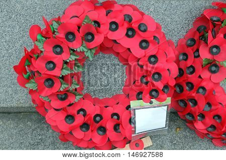 Red Plastic Poppy Flowers Remembrance Wreath at Monument