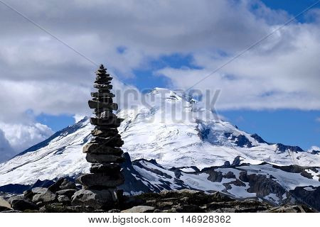 Stone cairn silhouette against icy peak of Mount Baker.  Cascade Mountains. Mount Baker National Forest. Seattle. Washington. USA.