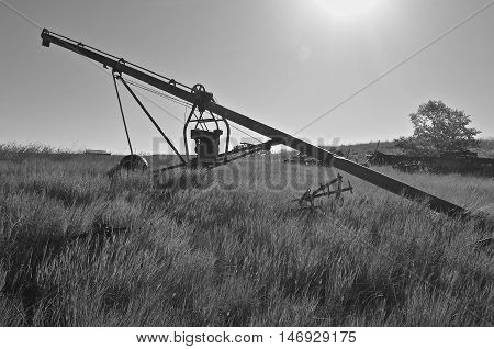 A silhouetted old tube grain elevator powered by a suspended gas engine is left in the long grass of a hilly pasture.