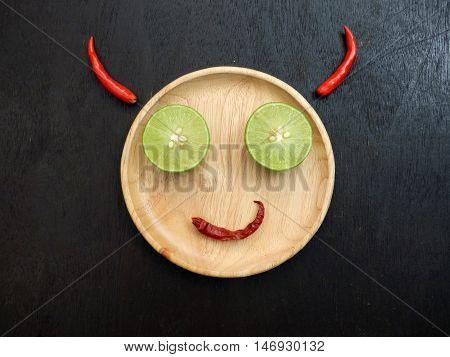 Feeling concept. Devil smile wooden plate is face lemon slice is eye red dried chilli is mouth and red chilli horn