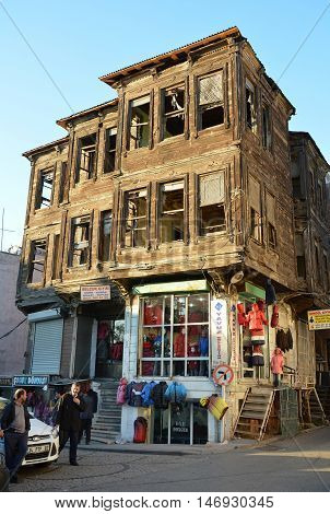 Istanbul, Turkey - November 4, 2015. Old Ottoman house in Istanbul, with commercial properties on the ground floor and people.