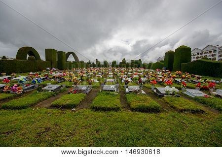 TULCAN, ECUADOR - JULY 3, 2016: lots of flowers adorn the tombs surrounded by plants sculptures.