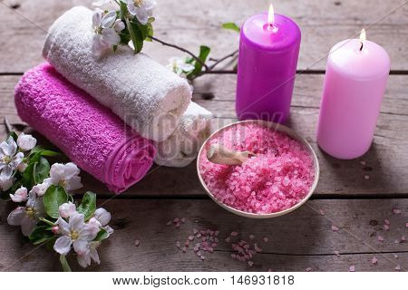 Spa or wellness setting. Sea salt in bowl towels candles and flowers on wooden background. Selective focus.