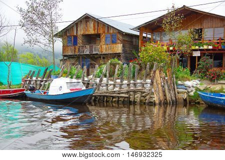 PASTO, COLOMBIA - JULY 3, 2016: blue and white small boat parken infront of some wood houses.