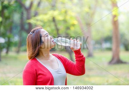 Portrait of young asian beautiful brown-haired woman wearing red t-shirt drinking water at summer green park.