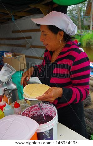 PASTO, COLOMBIA - JULY 3, 2016: unidentified woman preparing a dessert made of wafers, marmalade and caramel.