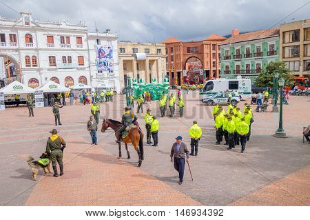 PASTO, COLOMBIA - JULY 3, 2016: some pedestrians walking trough the central square while the police is getting ready for an exhibition.