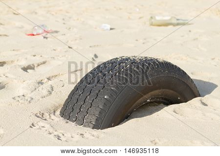 Abandoned tire embedded in the sand beach of a harbor .