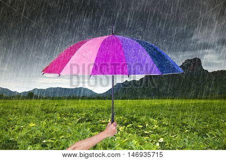 Hand Holding Multicolored Umbrella With Falling Rain At Khao Jeen Lae, Mountain At Lopburi, Thailand