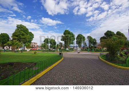 TULCAN, ECUADOR - JULY 3, 2016: cobble road that ends in a monument in the middle of a park.
