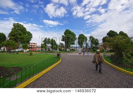 TULCAN, ECUADOR - JULY 3, 2016: unidentified man walking trough the park on the cobble road.